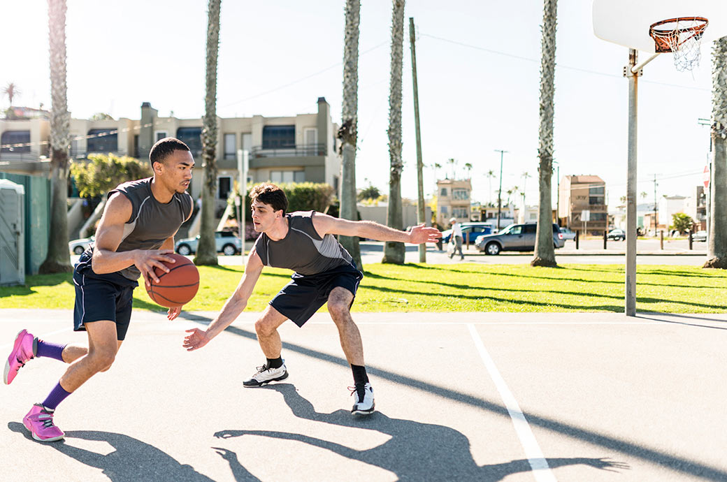 Two guys playing basketball at the park