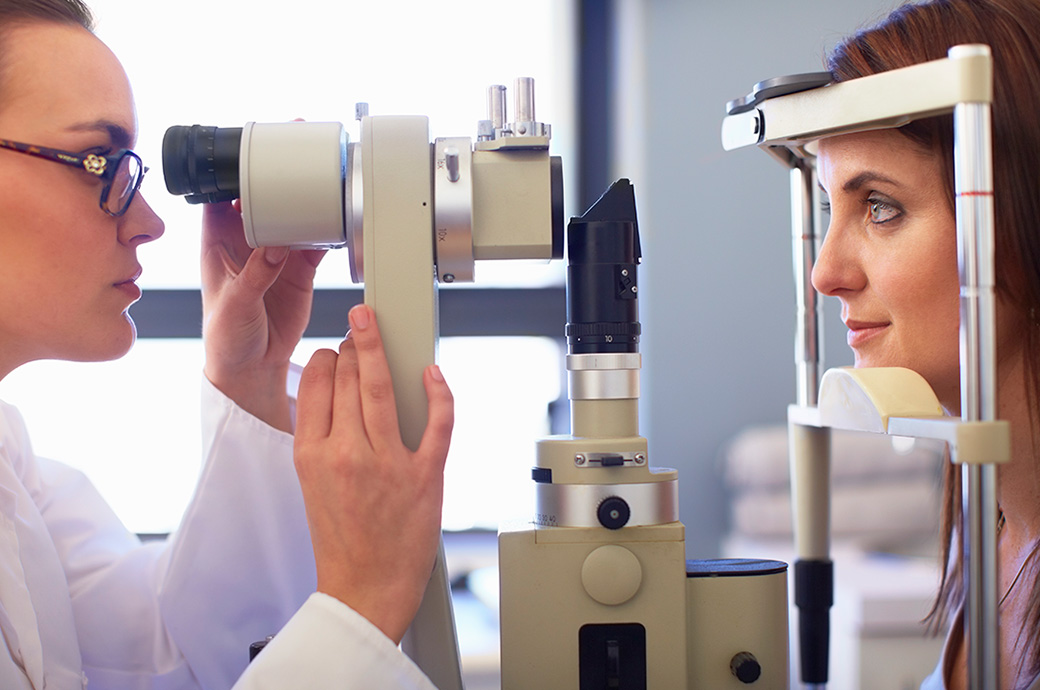 A side view of an optician and a young woman looking through a retinal camera