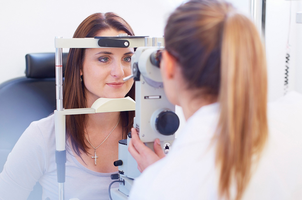The camera focuses on a young woman looking through a retinal camera as her optician looks through the other side